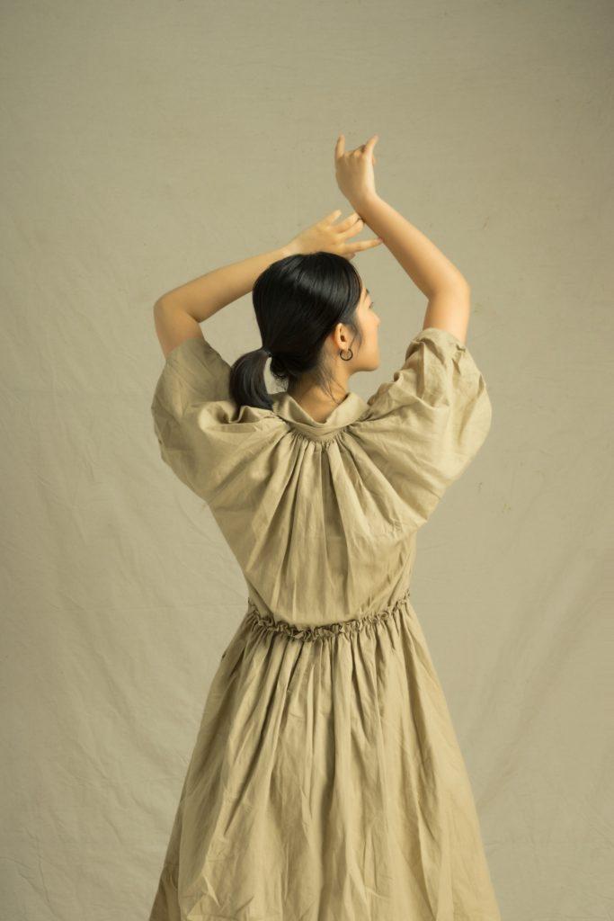 fille en robe vintage marron bras en l'air